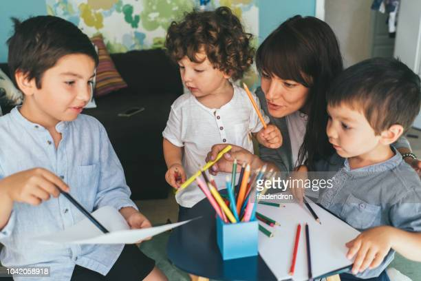 mother and sons drawing together - nanny stock pictures, royalty-free photos & images