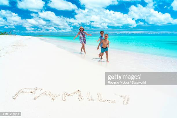 mother and sons happy on pink sand beach, caribbean - antigua & barbuda stock pictures, royalty-free photos & images