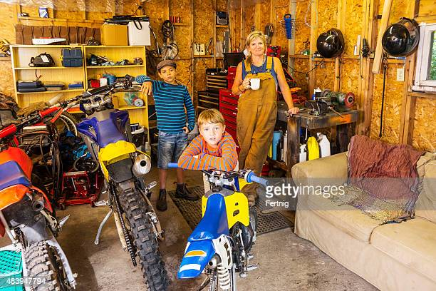 Mother and sons in their motorcycle dirt bike garage
