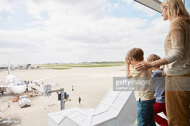 Mother and sons looking out of airport window