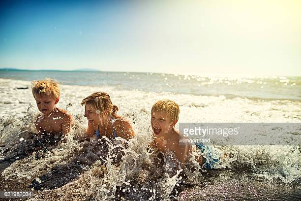 Mother and sons lying on beach splashing in sea waves