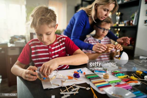 mother and sons making cell models of for school - craft stock pictures, royalty-free photos & images