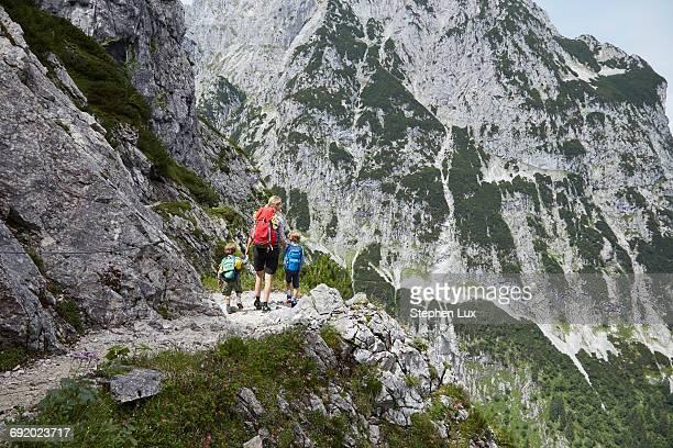 mother and sons trekking along mountainside, h_llental, zugspitze, garmisch-partenkirchen, bavaria, germany - oberbayern stock-fotos und bilder