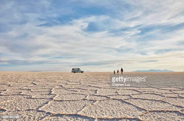 mother and sons walking across salt flats, recreational vehicle in background, salar de uyuni, uyuni, oruro, bolivia, south america - salt flat stock pictures, royalty-free photos & images
