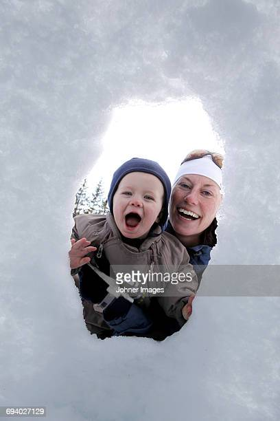 mother and sun playing in the snow - peeping holes ストックフォトと画像