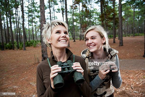 Mother and teen daughter enjoying scenic view with binoculars