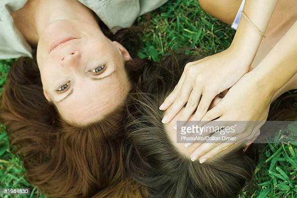 Mother and teen daughter lying on the ground together, girl covering face with hands, woman smiling at camera