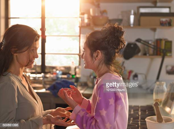 A mother and teenage daughter chatting playfully