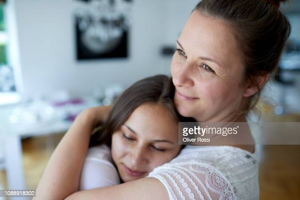 mother and teenage daughter embracing at home - tochter stock-fotos und bilder