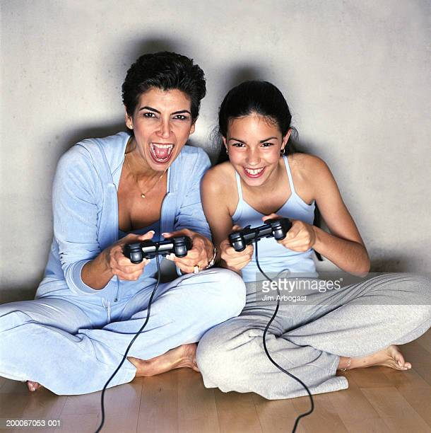 Mother and teenage daughter (12-14) playing video games at home