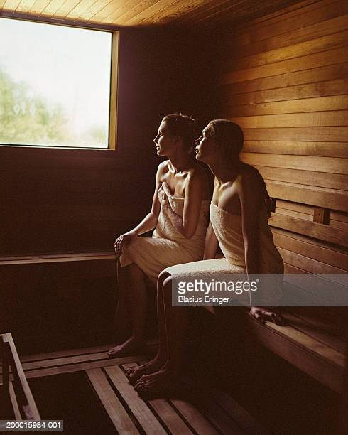 Mother and teenage daughter (13-15) sitting in sauna