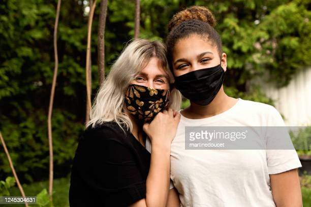 """mother and teenage daughter smiling behind protective face mask. - """"martine doucet"""" or martinedoucet stock pictures, royalty-free photos & images"""