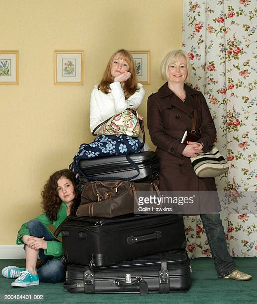 Mother and teenage daughters with luggage, portrait