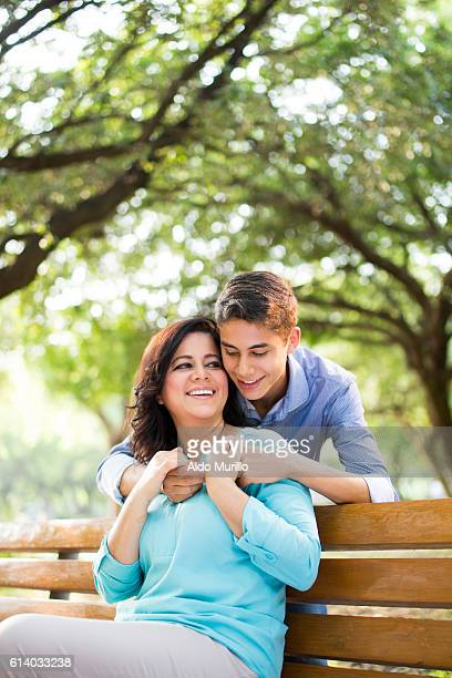 mother and teenage son holding hands and smiling - mexican mom stock photos and pictures