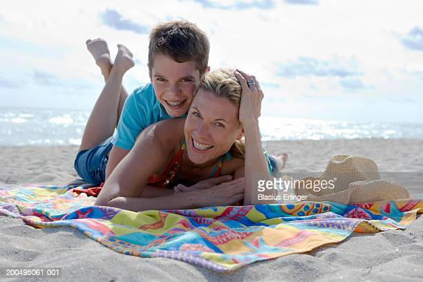 mother and teenage son (12-14) on blanket at beach, portrait - blasius erlinger stock pictures, royalty-free photos & images