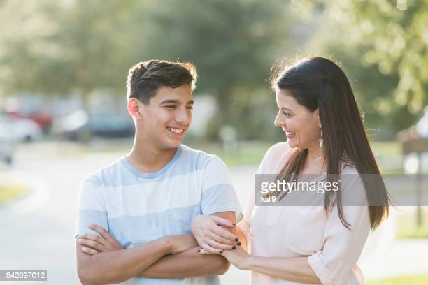 mother and teenage son standing outdoors - mother and son stock photos and pictures