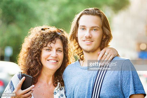 Mother and teenaged son Summer urban portrait with phone