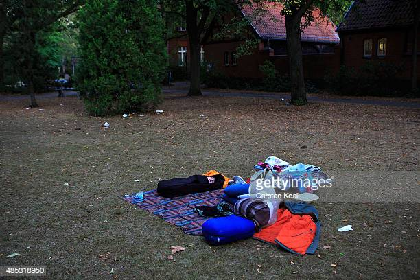 A mother and their baby lies in their stuff on the dirty ground in the Central Registration Office for Asylum Seekers of the State Office for Health...