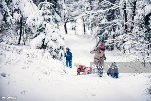Mother and three kids having fun in winter forest