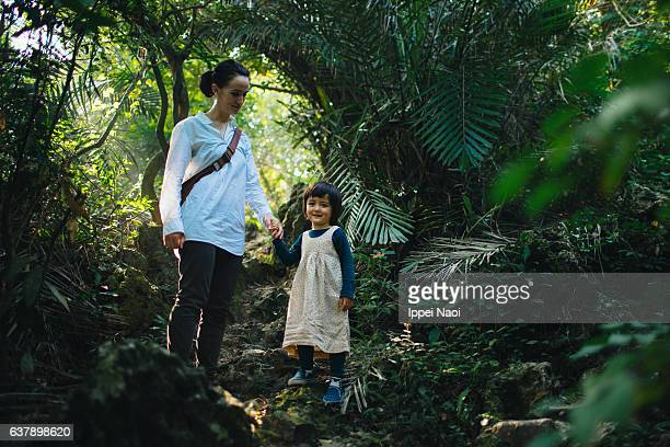 Mother and toddle girl hiking in forest, Taiwan