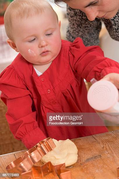 Mother and toddler baking Christmas biscuits