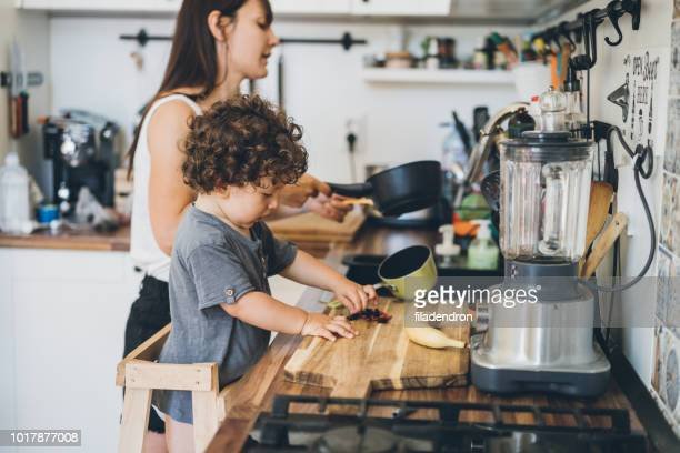 mother and toddler boy cooking - stereotypical homemaker stock pictures, royalty-free photos & images