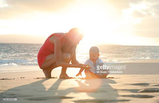 mother and toddler boy playing in beach - baby m stock pictures, royalty-free photos & images