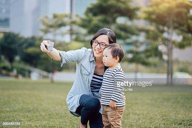 Mother and toddler boy taking selfies in the park