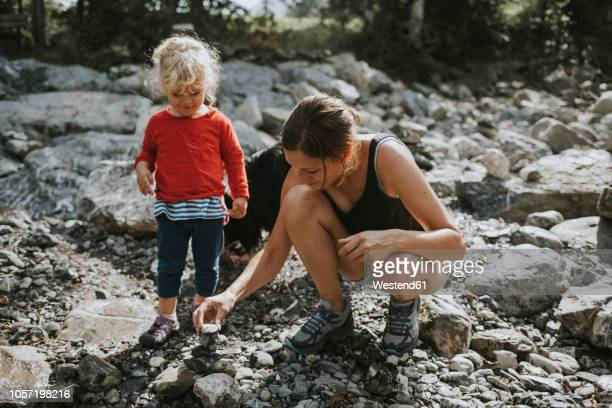 mother and toddler building a heap of stones - 石塚 ストックフォトと画像