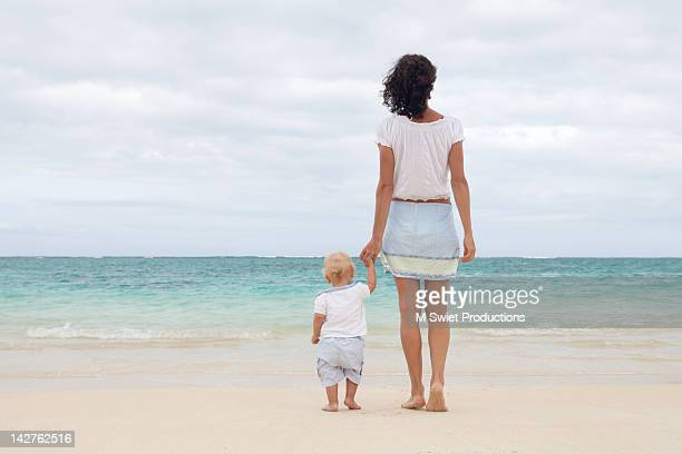 Mother and toddler child standing on beach