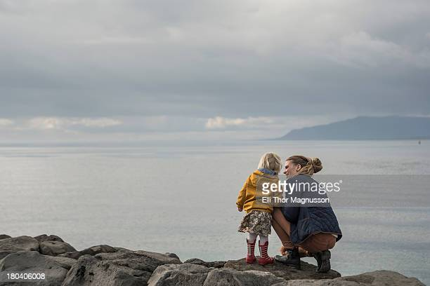 Mother and toddler crouching on harbor wall