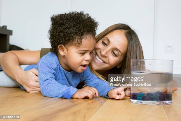 mother and toddler daughter looking at pet goldfish - anne sophie mutter stock-fotos und bilder