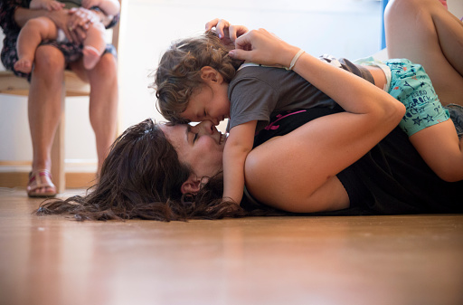 Mother and toddler lying on the floor playing - gettyimageskorea