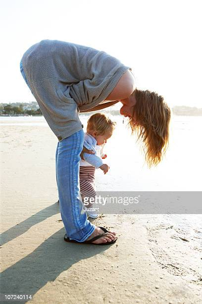mother and toddler on the beach - girl wear jeans and flip flops stock photos and pictures