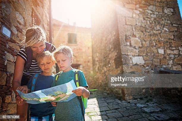 mother and tourist sons checking map in an italian town - tourisme photos et images de collection