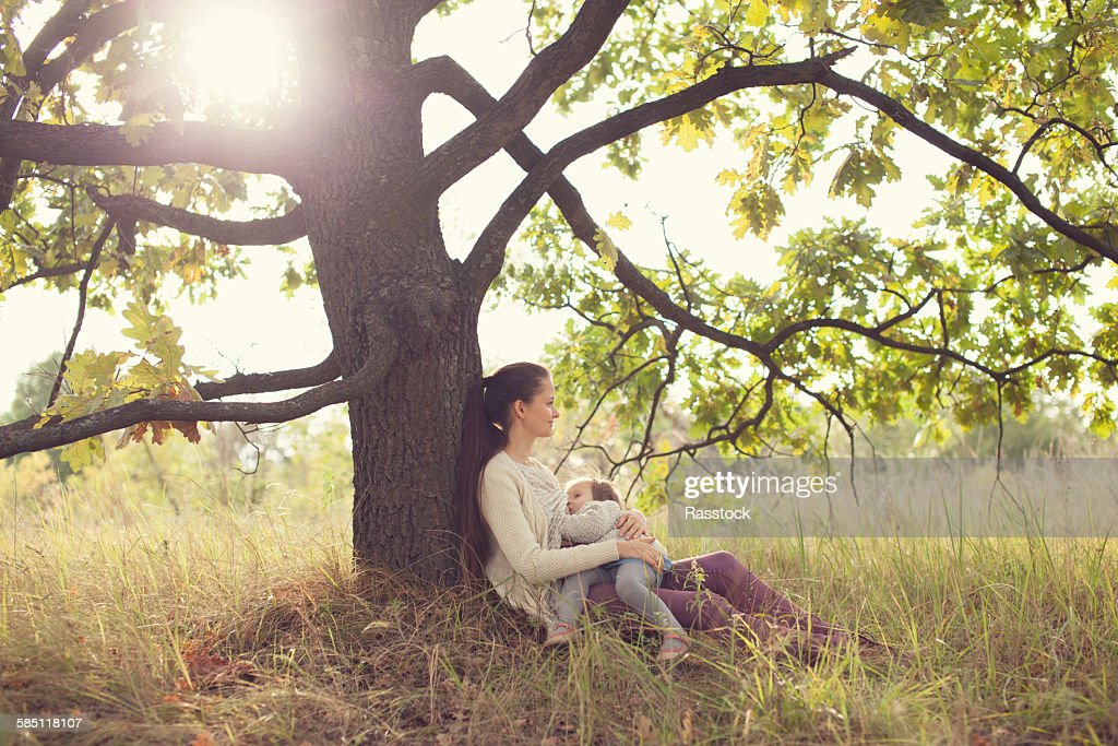 Mother and toyoung moddler girl have rest outdoors : Stock Photo