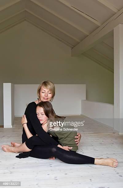 Mother and twelve year old daughter hugging on floor