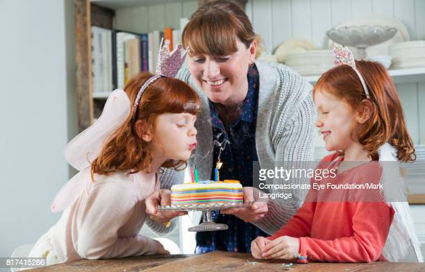 Mother and twin daughters blowing out candles on birthday cake in kitchen