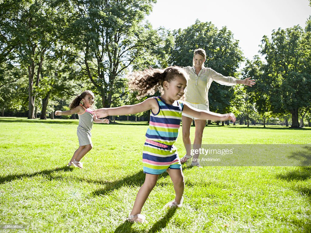 Mother and twin daughters playing in park : Stock Photo