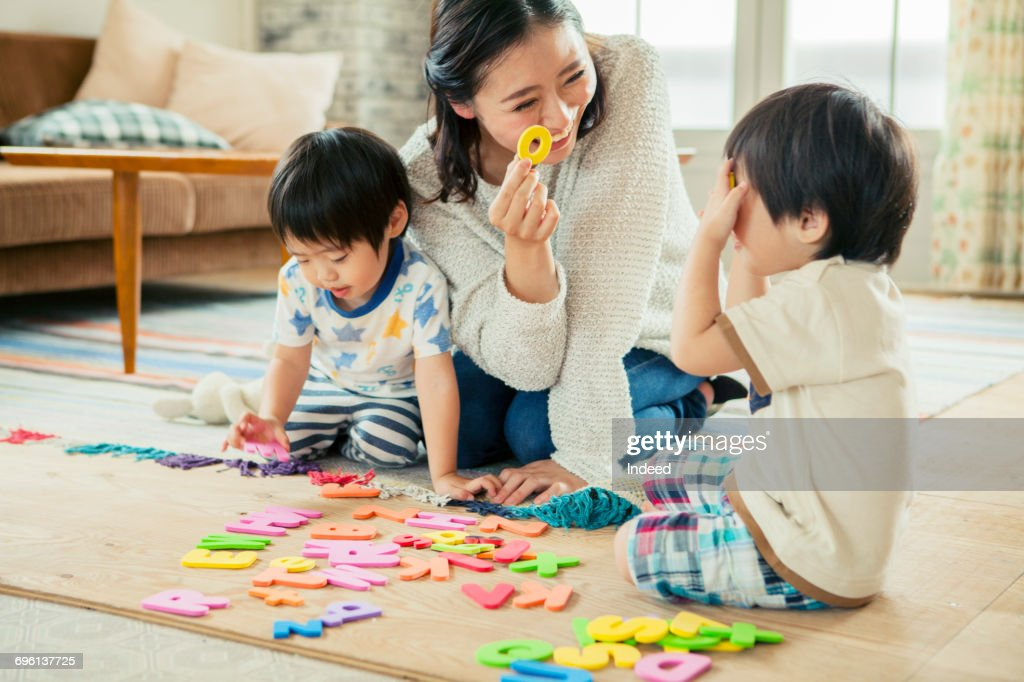 Mother and two boys playing with alphabet puzzles on floor : ストックフォト