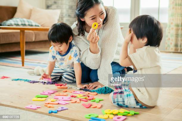 Mother and two boys playing with alphabet puzzles on floor