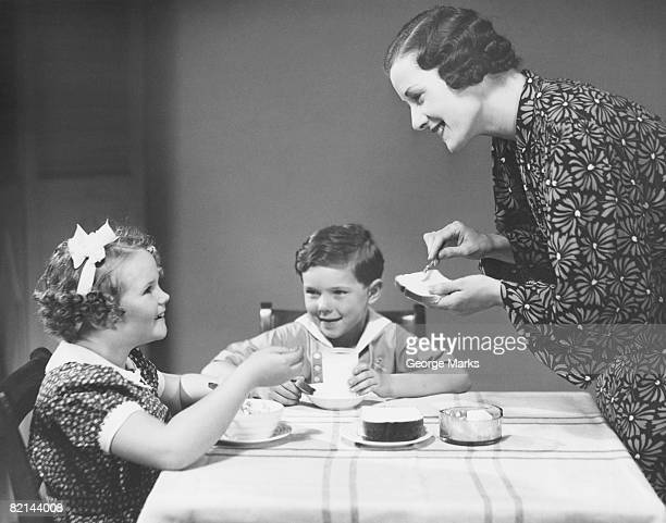 mother and two children (6-7) at breakfast table, (b&w) - permed hair stock photos and pictures