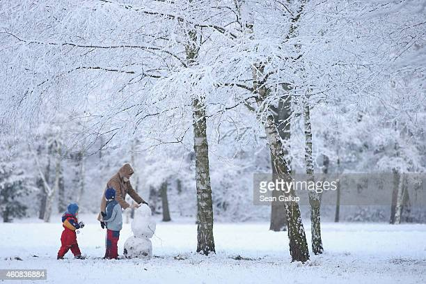 A mother and two children build a snowman in a snowcovered park in Zehlendorf district during the season's first snowfall on December 26 2014 in...