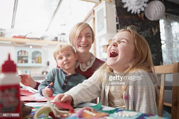 mother and two children craft making at kitchen table - arti e mestieri foto e immagini stock