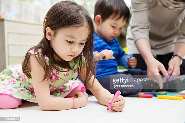 Mother and two children drawing in garden