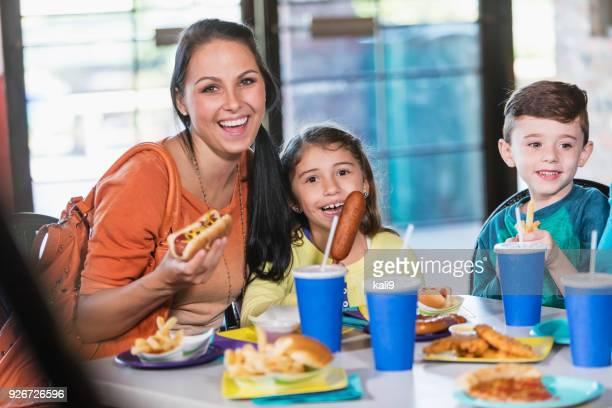 Mutter und zwei Kinder essen Fast food