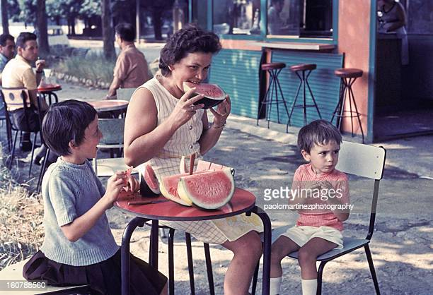 mother and two children eating watermelon outdoors