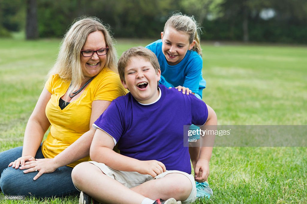 Mother and two children laughing in the park : Stock Photo