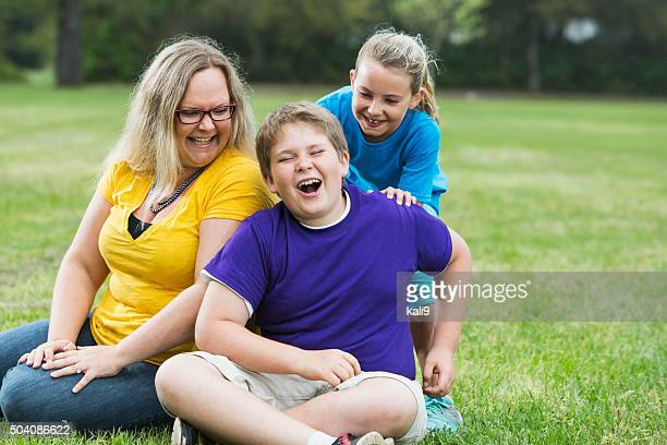 mother and two children laughing in the park - chubby boy stock photos and pictures