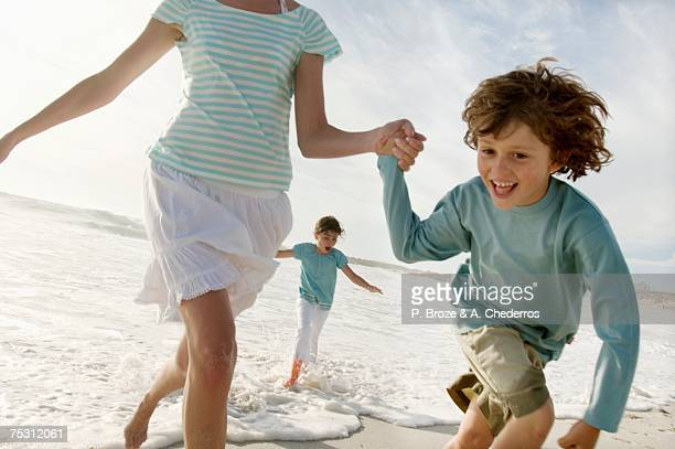 Mother and two children running on the beach, outdoors
